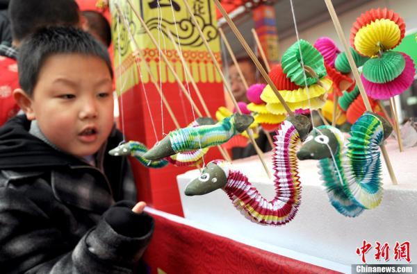 一种纸蛇玩具吸引着小朋友. 郝群英 摄