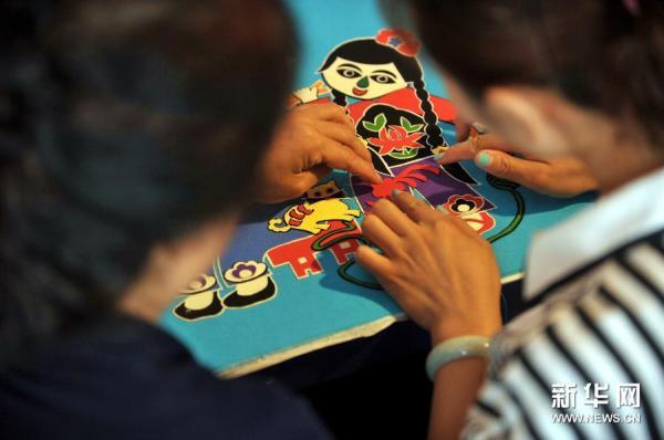 俗文化研发中心,两名工作人员在制作布贴画样品(9月13日摄).